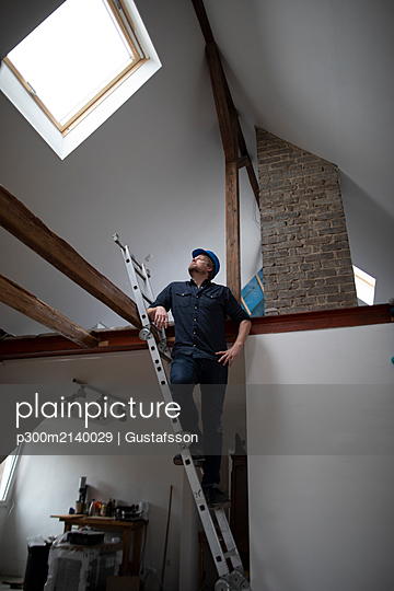 Architect working on construction sit of a loft conversion, standing on ladder - p300m2140029 by Gustafsson