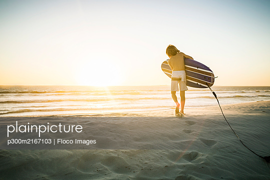 Rear view of boy with surfboard running on the beach at sunset - p300m2167103 by Floco Images