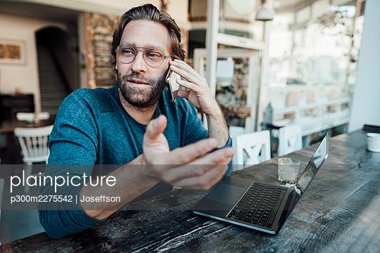 Male entrepreneur talking on mobile phone by laptop in coffee shop - p300m2275542 by Joseffson
