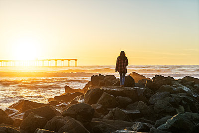 Rear view of woman standing on rocky shore against sky during sunset - p1166m1423351 by Cavan Images