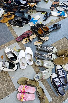 Getragene Schuhe vor einem Kloster in Chiang Mai - p177m1039894 von Kirsten Nijhof