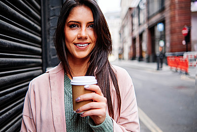Smiling young woman with disposable coffee cup standing by shutter in city - p300m2273663 by Angel Santana Garcia