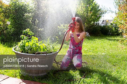 Girl with garden hose in summer - p300m1587418 von Sandra Roesch