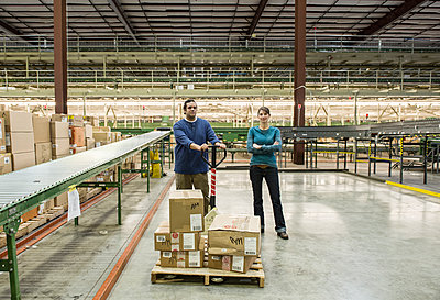 Caucasian male and female workers in a large distribution warehouse. - p1100m2002284 by Mint Images