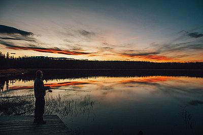 Canada, British Columbia, man fishing at Duhu Lake at sunset - p300m1568034 by Gustafsson