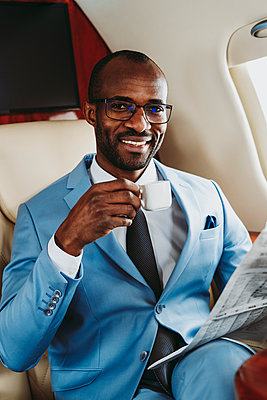 Happy businessman with coffee cup and newspaper in airplane - p300m2257037 by OneInchPunch
