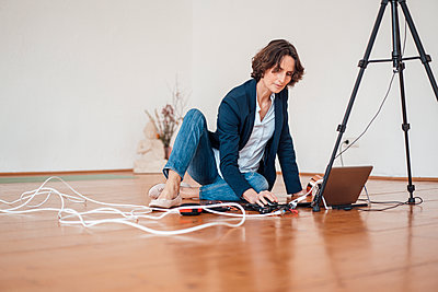 Mature businesswoman using laptop while sitting on floor at home office - p300m2267787 by Robijn Page