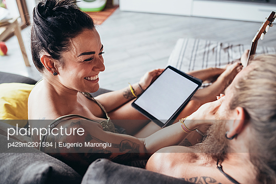 Bearded tattooed man with long brunette hair and woman with long brown hair sitting on a sofa, looking at digital tablet. - p429m2201594 by Eugenio Marongiu