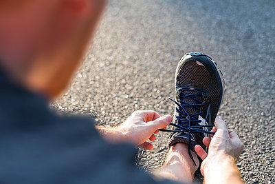 Jogger schnürt seinen Schuh - p1396m1463543 von Hartmann + Beese