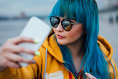 Portrait of young woman with dyed blue hair taking selfie with smartphone - p300m2062872 by Vasily Pindyurin