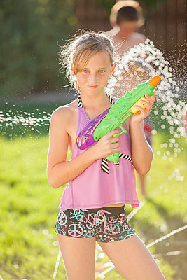 Caucasian girl holding a water gun - p555m1479001 by Mike Kemp