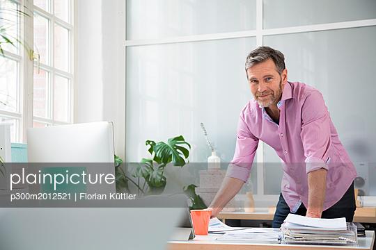 Portrait of a man working at desk in office - p300m2012521 von Florian Küttler