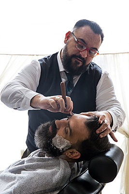 Barber shaving a man using a straight razor - p300m1205881 by Andrés Benitez