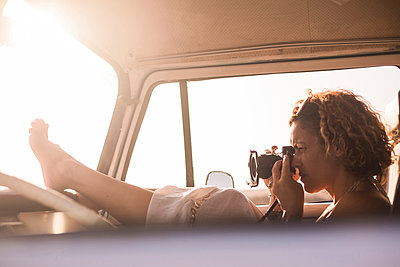 Woman sitting in parked van taking picture at sunset - p300m1505796 by Simona Pilolla