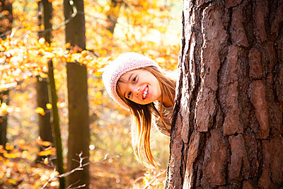 Young girl behind tree in autumn - p300m2081092 by Larissa Veronesi