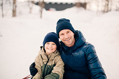 Portrait of cheerful father with arm around son during winter - p426m2279920 by Maskot