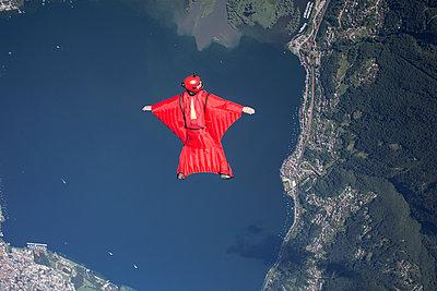 Wingsuit skydiver pilot flying over lake, Locarno, Tessin, Switzerland - p429m1175386 by Oliver Furrer