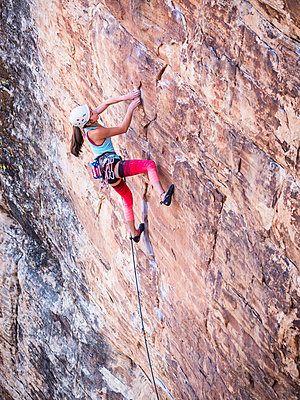 Mixed race girl rock climbing on cliff - p555m1312135 by Don Mason