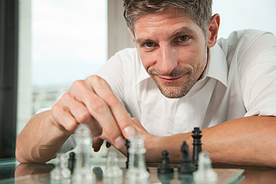 Portrait of a man in a bureau playing chess - p770m661523 by mbphoto