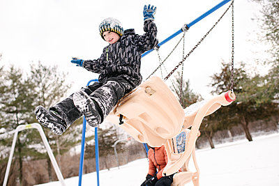 Boy jumping from playground swing in snow - p924m2074517 by Viara Mileva