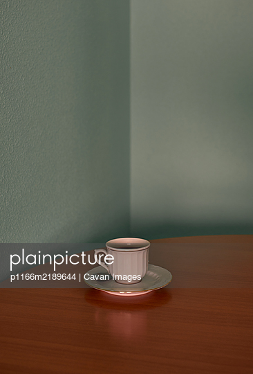 Coffee cup on a corner table. Conceptual image - p1166m2189644 by Cavan Images