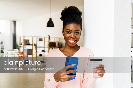 Young woman with credit card smiling while shopping through mobile phone standing at home - p300m2251378 by Giorgio Fochesato