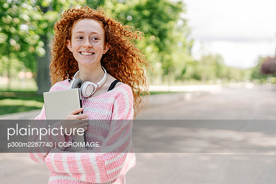 Barcelona, Calaonia, Spain. Young woman walking in a park - p300m2287740 von COROIMAGE