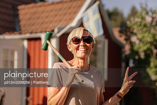 Happy woman holding croquet mallet - p312m2208256 by Plattform
