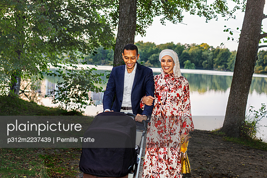 Couple with pram walking at lake - p312m2237439 by Pernille Tofte