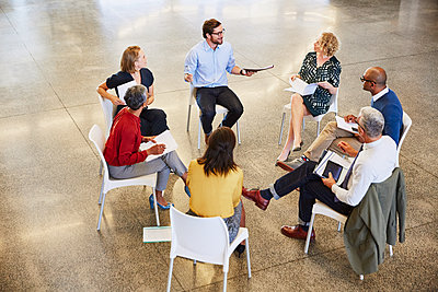 Business people talking in circle meeting - p1023m1192575 by Ryan Lees