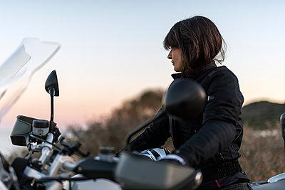 Female biker watching the panorama at sunset - p1165m1541059 by Pierro Luca