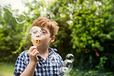 Thoughtful boy blowing bubbles in yard - p1166m1150481 by Cavan Images