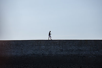 Man walking on the seawall - p1402m1474962 by Jerome Paressant