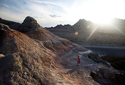 A young woman, wearing pink, runs along an unmarked trail in Badlands National Park at sunset. - p1424m1501792 by Michael Hanson