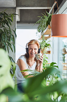 Happy woman holding coffee cup while listening music through headphones while sitting in loft apartment - p300m2265344 by Jo Kirchherr
