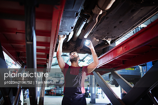 Male mechanic with flashlight working under car in auto repair shop - p1023m2196752 by Tom Merton