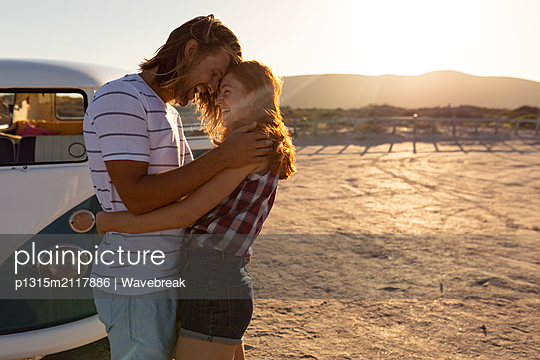 Happy young couple embracing each other near camper van at beach - p1315m2117886 by Wavebreak
