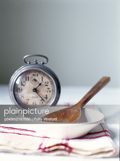 Metal alarm clock with wooden spoon in bowl. - p349m2167690 by Polly Wreford