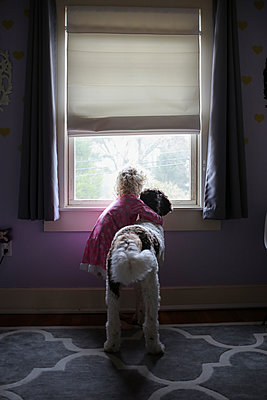 Girl with dog looking through window at home - p1166m1230411 by Cavan Images