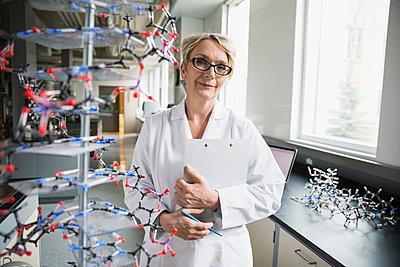 Portrait confident scientist behind molecule model in laboratory - p1192m1036741f by Hero Images