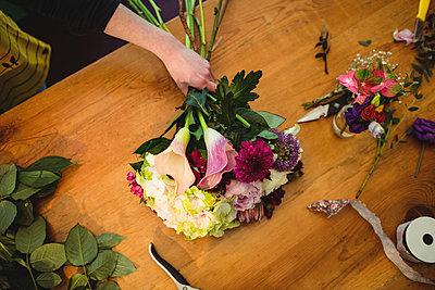 Female florist preparing a flower bouquet at her flower shop - p1315m1199867 by Wavebreak