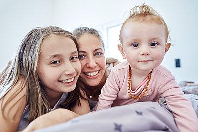 Portrait einer Mutter mit Tochter und Baby im Bett - p1359m1221634 von Great Images