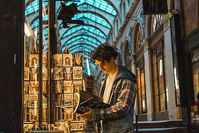 Young man looking at book - p300m1567711 by VITTA GALLERY