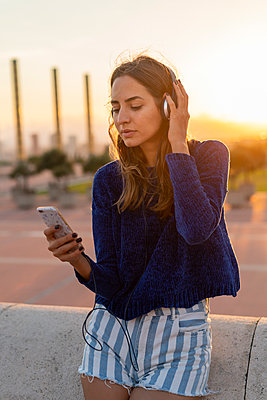 Spain, Barcelona, Montjuic, young woman with cell phone and headphones at sunset - p300m2058605 by VITTA GALLERY