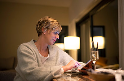 Blond woman working late while using digital tablet in illuminated living room - p300m2188175 by Bernd Friedel