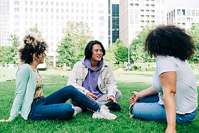 Young man talking to multi ethnic female friends at park - p300m2293264 by Angel Santana Garcia