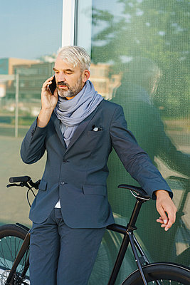Businessman with bicycle talking on mobile phone while standing against glass building - p301m1498735 by Halfdark