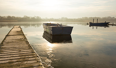 A rowing boat floats adrift on a frozen lake beside an empty walkway at Hornsea Mere, East Yorkshire, Yorkshire, England, United Kingdom - p871m2101559 by Chris Cook