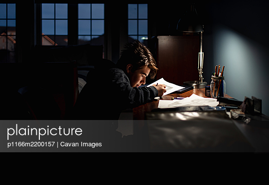 Teenage boy drawing at a desk in a dark room by lamp light. - p1166m2200157 by Cavan Images