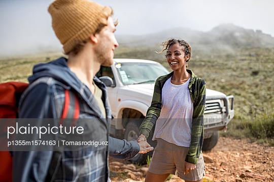 Junges Paar auf Bergtour mit SUV im Hintergrund - p1355m1574163 von Tomasrodriguez
